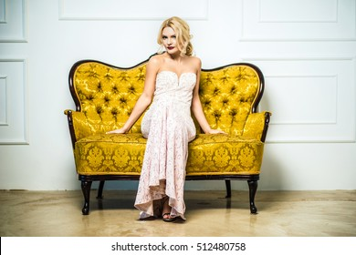 High fashion. shapely blonde in silk evening gown. Femininity