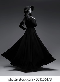 High fashion shot of elegant woman in a hat and long fluttering dress. Black and white image