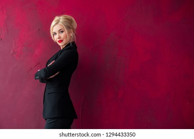 High fashion shot of sexy blond woman in black suit on red background, Portrait of elegantly dressed gorgeous business woman with red lips