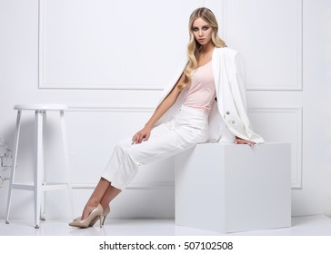 High fashion shot of young blond woman in white suit on white background.
