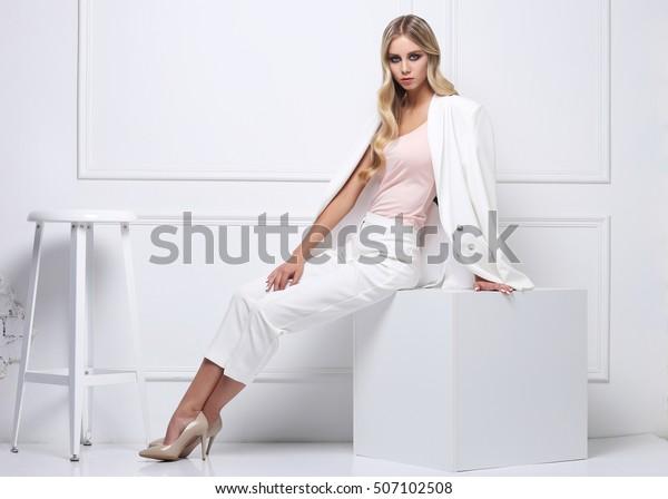 Imagen de alta moda de una joven rubia vestida con traje blanco sobre fondo blanco.