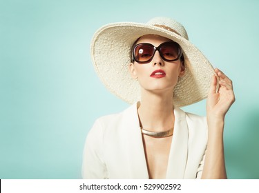 High fashion studio portrait of female wearing hat.