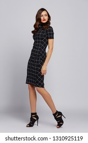 high fashion woman in black chekered dress. Curly hair, black shoes, posing in studio