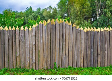 High fence with solid beams, pointed ends from the top, blue sky, a sunny summer day countryside