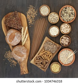 High fiber health food with whole grain bread, pasta, cereals and grains on an olive wood board and in wooden and terracotta bowls. Rustic background on oak, top view.