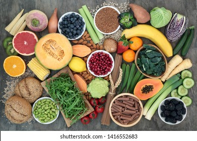 High fibre food for good health concept with fruit, vegetables, seeds, nuts, whole wheat pasta and whole grain seeded rolls. Foods high in antioxidants, omega 3, anthocyanins & vitamins.