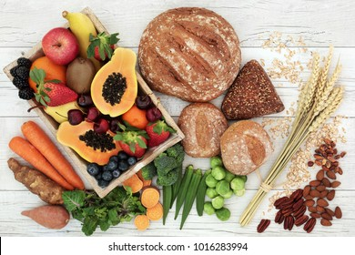 High fibre health food concept with fresh fruit, vegetables, wholegrain bread, nuts and cereals. Foods high in antioxidants, anthocyanins, omega 3 fatty acids and vitamins.