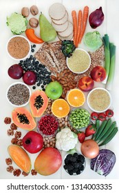 High fibre health food concept with vegetables, fruit whole grain crackers, seeds, nuts, grains & pulses. Foods with omega 3, antioxidants, anthocyanins, vitamins & minerals. Top view on  rustic wood.