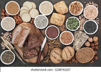 High fibre health food with whole grain bread and rolls, whole wheat pasta, grains, nuts, seeds, oatmeal, oats, crackers, barley and bran flakes on lokta paper background.