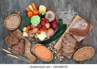 High fibre natural health food with whole grain rye bread and rolls, vegetables, legumes, seeds, nuts and grains on marble background. Full of antioxidants, anthocyanins, vitamins and omega 3.