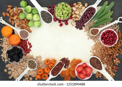 High fibre super food background border with fruit, vegetables, seeds, nuts, whole wheat pasta, cereals & grains. Foods with omega 3, anthocyanins, antioxidants & vitamins. On parchment paper & slate.