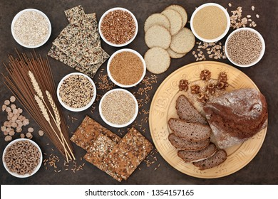 High fibre super food with whole wheat pasta, whole grain walnut and rye bread, crackers, seeds, nuts, grains, oatmeal, oats, barley and bran flakes with wheat sheath on lokta paper background.