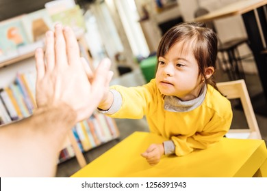 High five. Dark-eyed sunny child giving high five to her teacher in the inclusive kindergarten