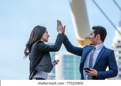 High five, two business people slapped hands during completed business plan talking on the city background.