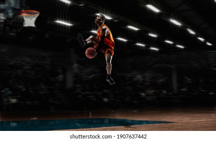 In high flight. African-american young basketball player in action and motion in flashlights over dark gym background. Concept of sport, movement, energy and dynamic, healthy lifestyle. Arena's