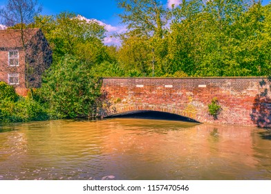 High flood water of the Great Stour river under a bridge in Canterbury, Kent, Uk on a sunny day after heavy rain
