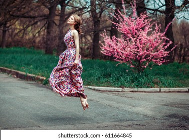 High flying success and joy for happy slim young woman wearing long dress, jumping into the air outdoors in countryside, enjoying spring sunshine in the park