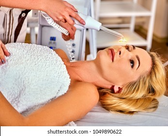 High frequency machine in spa salon. Young woman receiving electric darsonval facial massage after procedure at beauty room close up. Removal of acne from surface of face. Removing wrinkles.