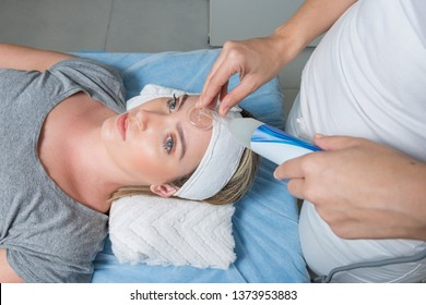 High frequency machine in spa salon. Young blond woman receiving electric darsonval facial massage after procedure at beauty room. Removal of acne from surface of face. Removing wrinkles.