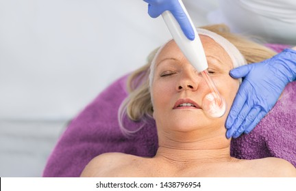 High frequency machine in spa salon. Senior woman receiving electric darsonval facial massage after procedure at beauty room close up.