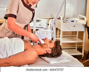 High frequency machine in spa salon. Man receiving electric darsonval facial massage after procedure at beauty room. Modern technologies and methods of rejuvenation.