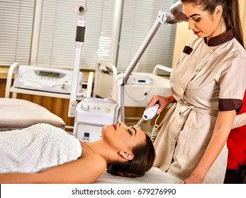 High frequency machine in spa salon. Young woman receiving electric darsonval facial massage after procedure at beauty room close up. Removal of acne from surface of face. How to preserve youth idea.