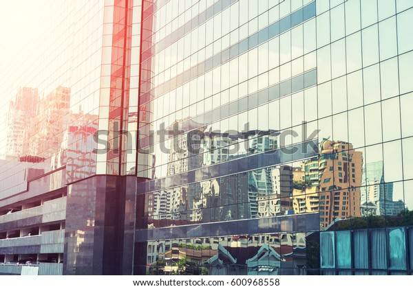 High glass modern building with blue sky and cloud at sunset for abstract background.Facades texture pattern for business background.