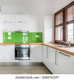 High gloss, white kitchen with big window, wooden countertop and modern, green backsplash