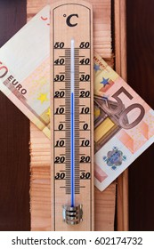 high heating costs, high expenses in cold winter, paper money behind a thermometer/paying for a warm house, heavy utility costs bill/working costs costing high amount of money, huge bill for heating