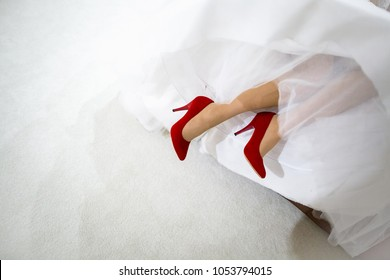 High heel red shoes, the bride in a white dress and red shoes on her heels lay on the bed, the beautiful legs of the bride, girl in red shoes