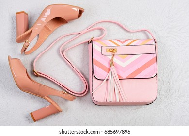 High heel sandals. Sandals and handbag on white background. Pair of shoes and bag in pink colour with perfume bottle. Fashion and beauty concept. Women's shoes and accessories, top view