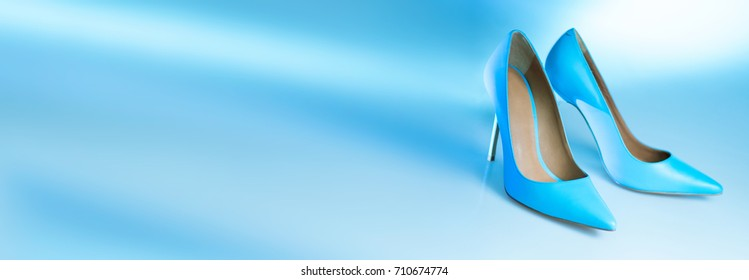 High heel shoes in blue color. Blue soft background.  Horizontal banner composition. Shop advertising. Fashion classic style.