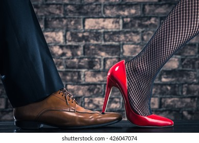 High heeled women are stepping on the shoes of the man
