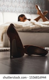 High heels in front of female bedroom defocused. Attractive sexy erotic woman relaxing on bed. Female erotic massage. Escort service. Desire concept. Erotic attribute. Foot fetish concept.