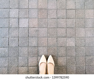 High Heels on Pavement Background, Top View. Selfie Female of Feet and Legs Seen from Above. Beautiful Fashion Woman Standing Wearing Beige Flat Shoes (Sandals) on Concrete Road or Tile Floor.