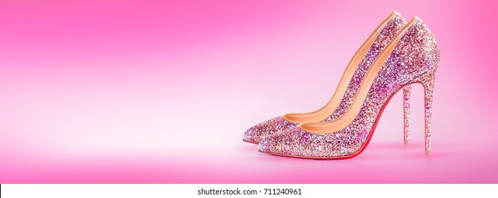 High heels in pink color. Woman pair of shoes on pink blurred background. Horizontal banner composition. Shop ad. Fashion modern style.