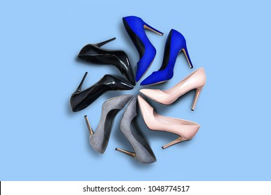 High heels. Top view different colors of high heels isolated blue pastel background. High heels arranged in a circle. Matt and shiny high heels. Fashion and beauty concept. Footwear for women.
