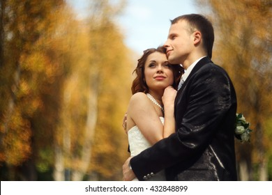 High hopes - wedding couple stands in an autumn park