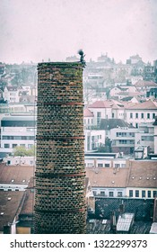 High industrial chimney with funny figure in the center of Trebic, Czech republic. Architectural theme. Travel destination. Analog photo filter with scratches.