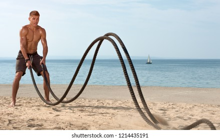 High intensive fitness workout. Young muscular man training with battle ropes on the beach against blue sky. Place for text.