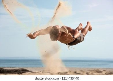 High intensive fitness workout. Young muscular man jumping on the beach against blue sky. Place for text.