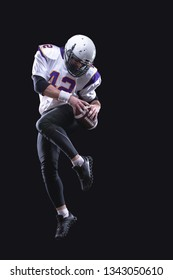 High jump of American Football Player, isolated on black background.