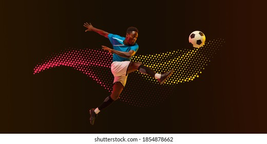 High jumping. Male soccer, football player training in action, kicking in jump isolated on dark lined background in neon light. Concept of motion, action. Neoned modern artwork, cover, flyer designed.