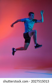 High jumps. Portrat of Caucasian professional male athlete, runner training isolated on pink studio background with blue neon filter, light. Concept of action, motion, speed, healthy lifestyle. - Shutterstock ID 2027515013