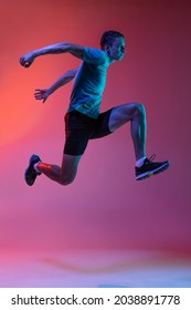 High jumps. Portrat of Caucasian professional male athlete, runner training isolated on pink studio background with blue neon filter, light. Concept of action, motion, speed, healthy lifestyle. - Shutterstock ID 2038891778