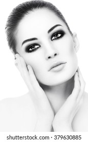 High key black and white portrait of young beautiful healthy woman with smoky eyes make-up touching her face