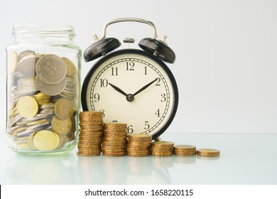 high key. business and finance management conceptual images. stacked money with clock, home replica, bottle of coins isolated against white background with reflection. copy space