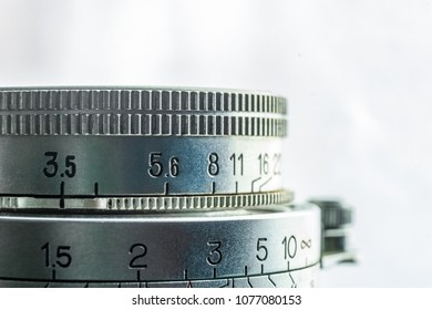 High key closeup of an old vintage camera lens with the engraved values of aperture, isolated on a white background with copy space. Photography and commercial concept.