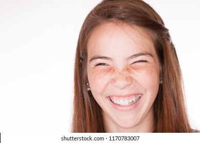 High Key faded film look head shot of a Brunette Tween Girl in the studio looking at camera with silly grin