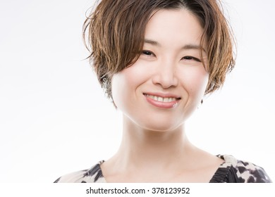 A high key headshot of a smiling, beautiful and young Japanese woman on a white background.